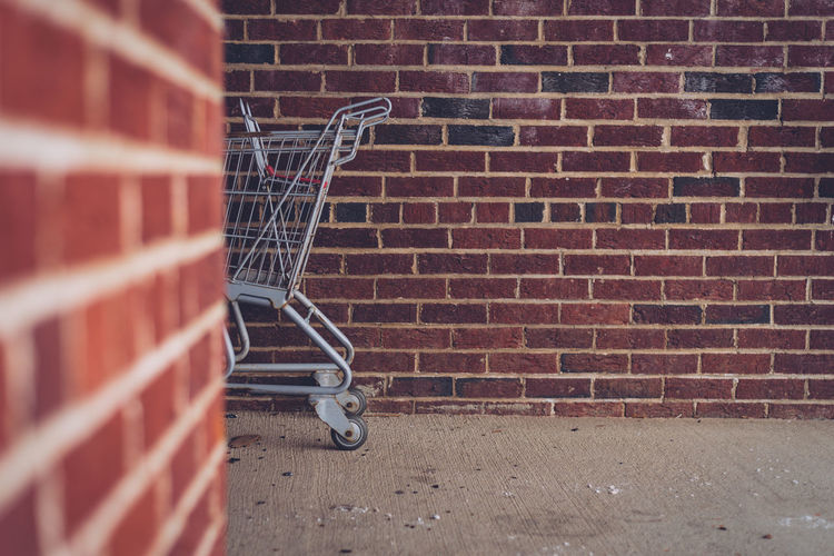 View of shopping cart against brick wall