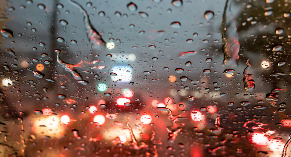 Blur night city life through windshield : Drops of rain on car's mirror upon traffic jam. Rain Backgrounds Car Car Interior Close-up Day Drop Droplet Focus On Foreground Full Frame Glass - Material Indoors  Land Vehicle Mode Of Transport Nature No People Rain RainDrop Rainy Season Transparent Vehicle Interior Water Water Drop Weather Wet Window
