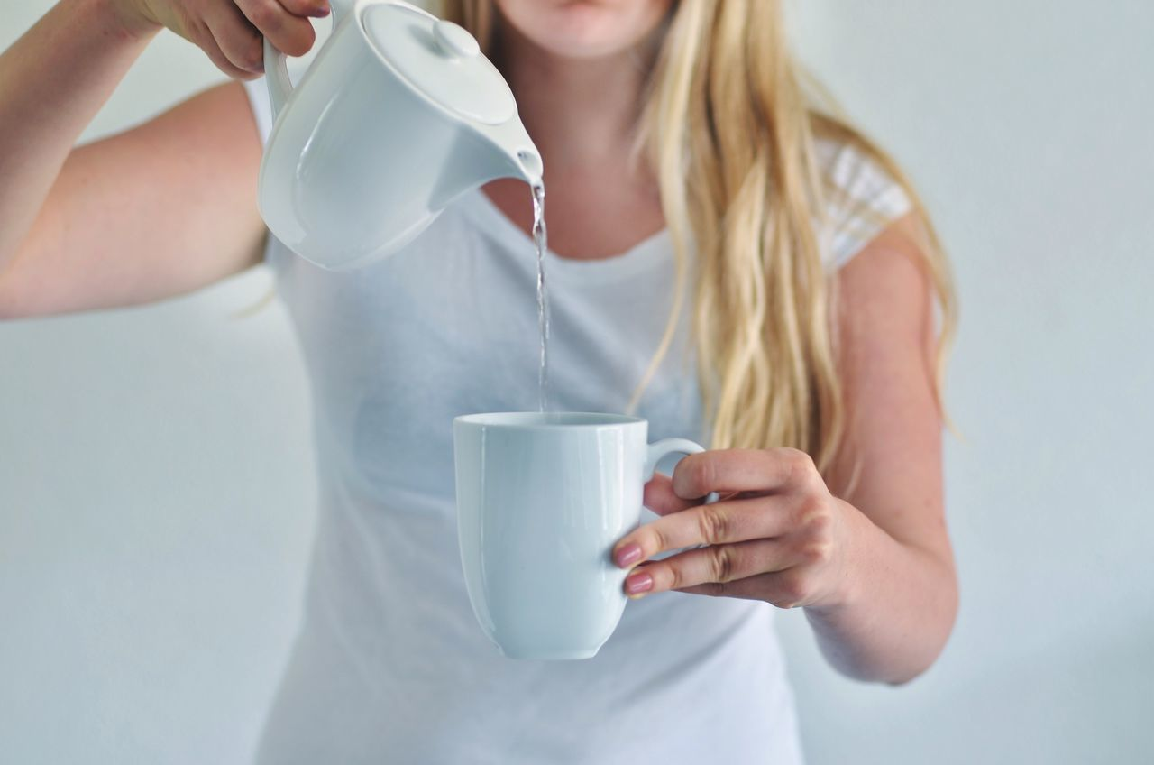 Midsection Of Woman Pouring Water In Cup Against White Background
