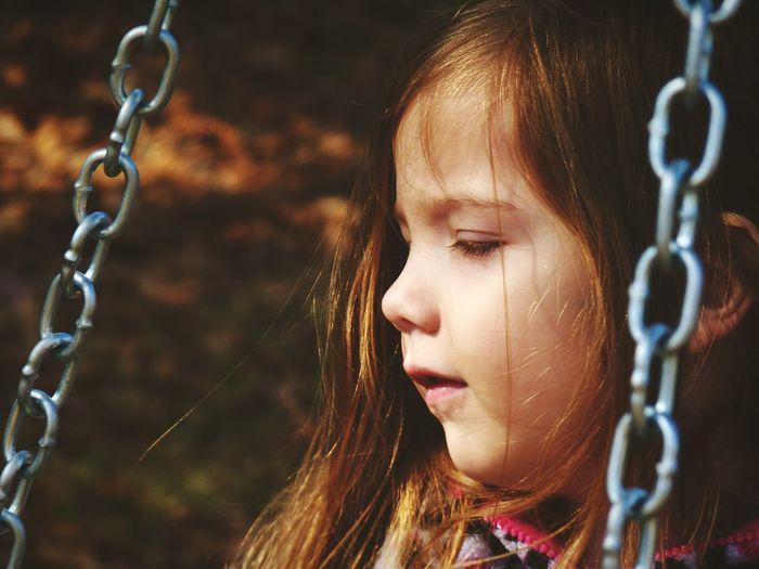Close-up of cute girl swinging at playground