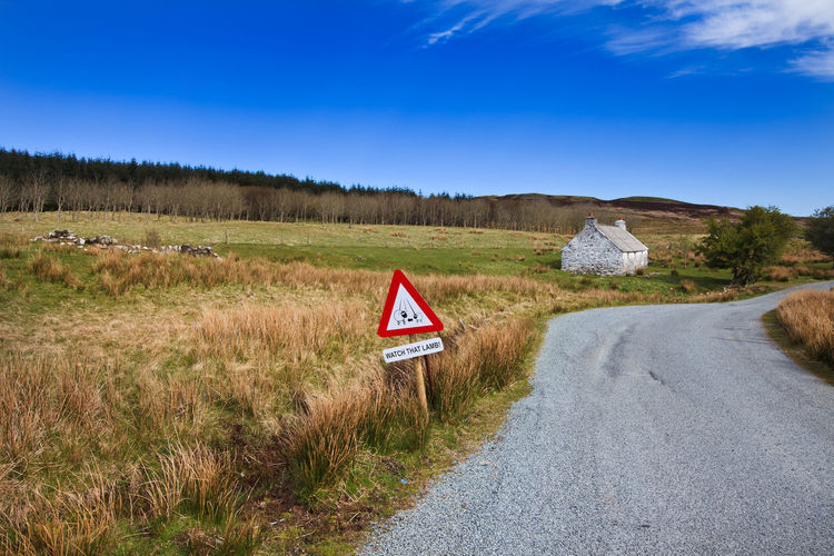 Road Signs On Landscape Against Blue Sky