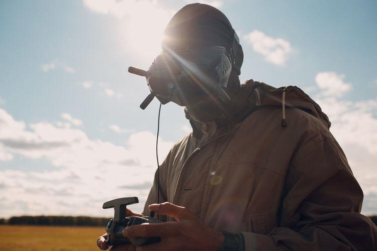 Man holding camera against sky