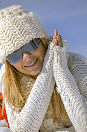 Smiling Young Woman Lying On Snow Against Sky