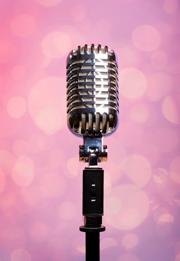 Close-Up Of Microphone Against Pink Background