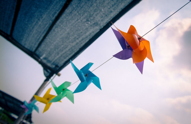 Low angle view of paper toy hanging against sky