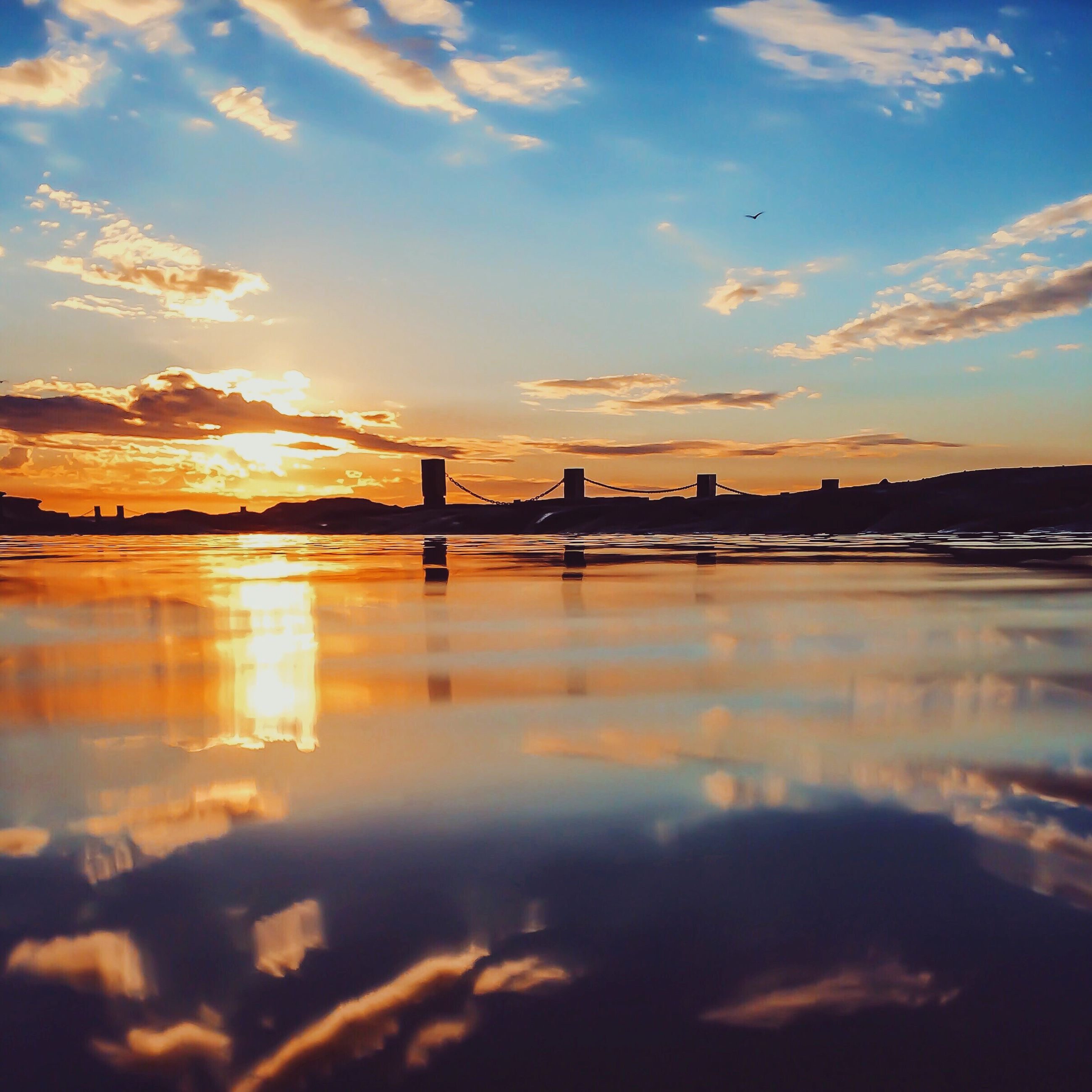 sunset, water, reflection, tranquil scene, scenics, tranquility, sun, idyllic, lake, sky, waterfront, cloud - sky, river, bridge - man made structure, calm, beauty in nature, cloud, nature, orange color, standing water, outdoors, sea, surface level, majestic, ocean, bridge, no people, remote