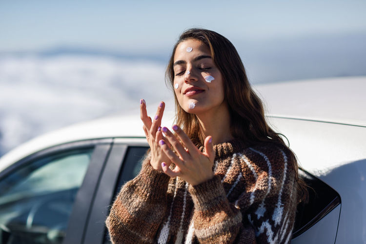 Young woman applying moisturizer on face during winter