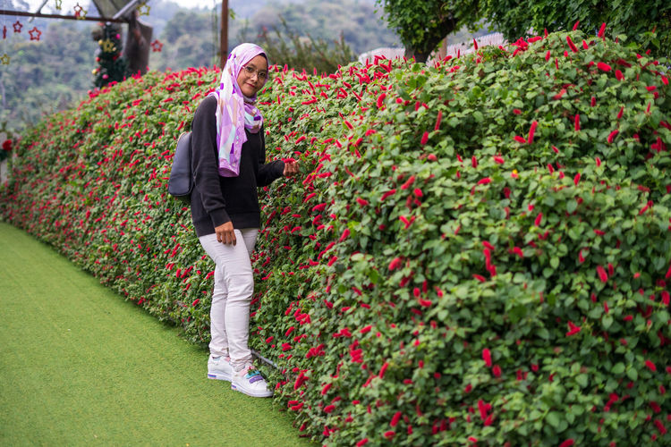 Full length of person standing by flowering plants