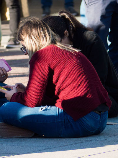 Rear view of two female friends sitting on floor in city