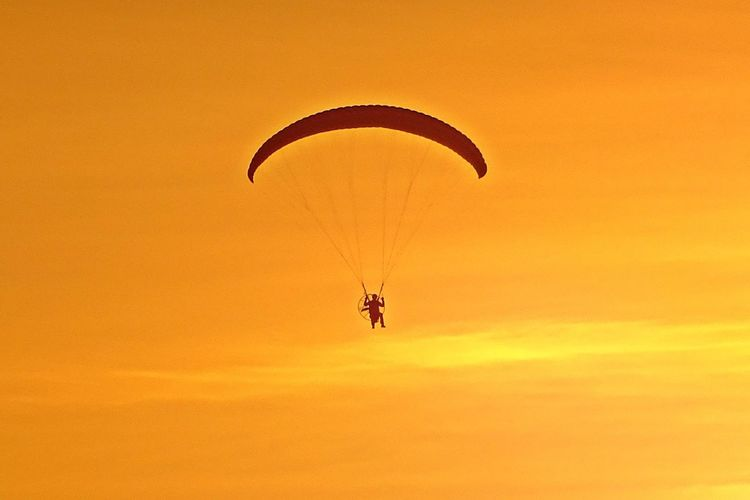 Low angle view of person paragliding against orange sky
