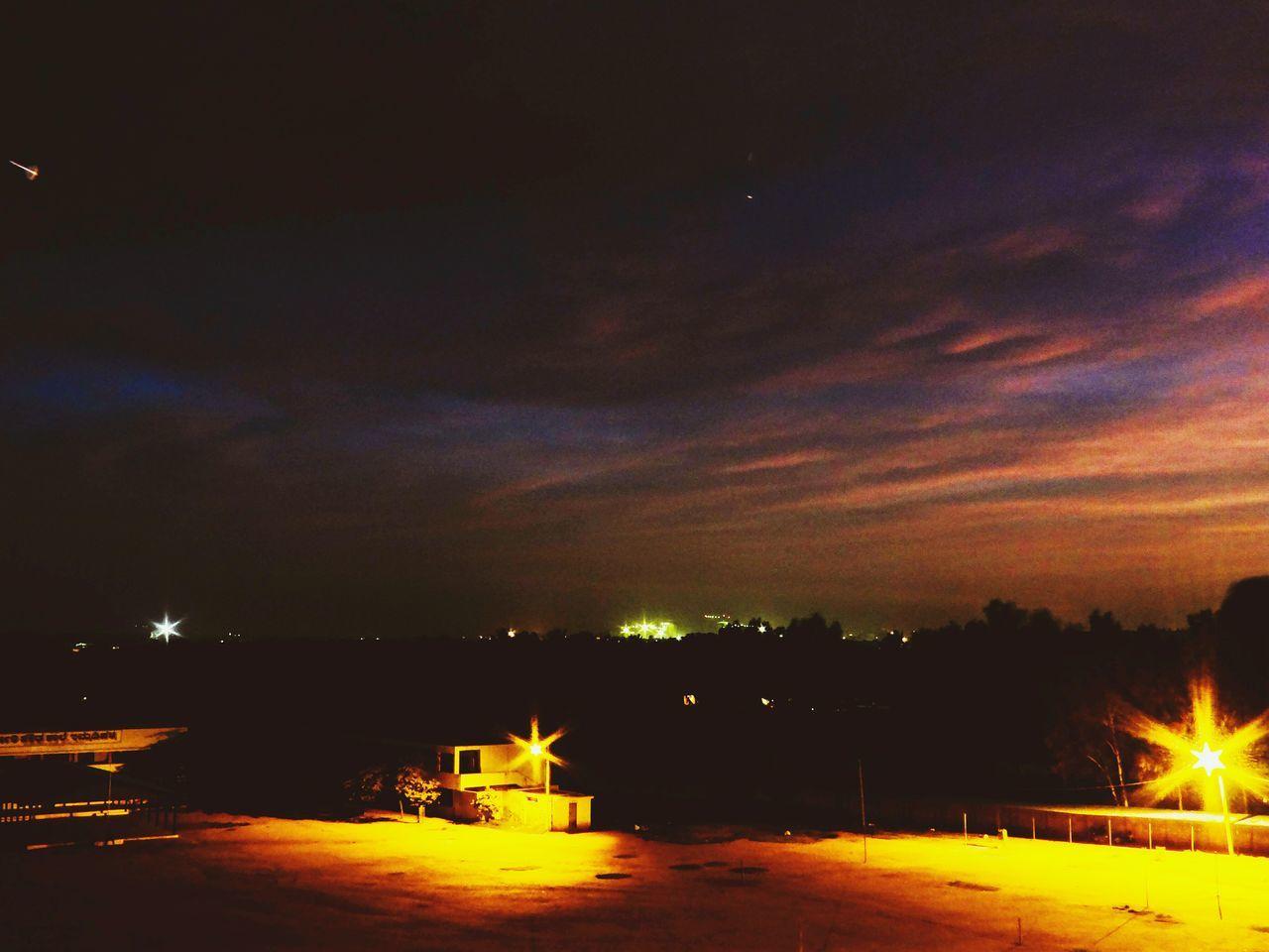 Lit lamps along road at night