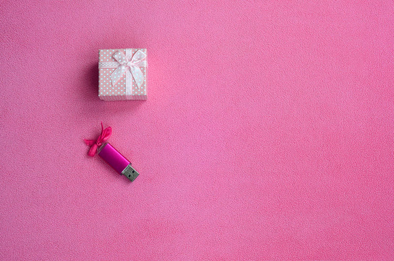 High angle view of usb stick and gift on pink background