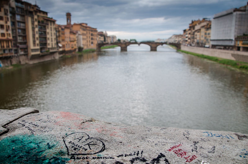 Graffiti On Retaining Wall By Arno River Against Cloudy Sky