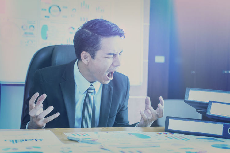 Angry businessman screaming in office