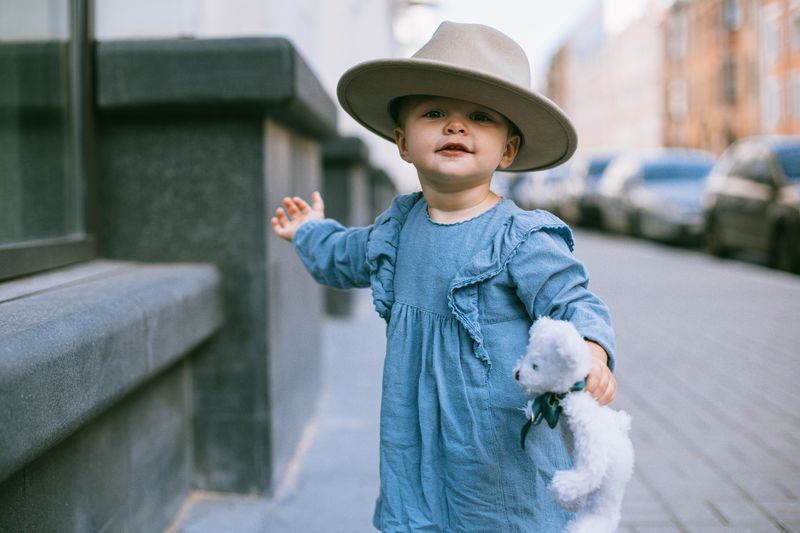 Cute girl wearing hat holding toy standing outdoors