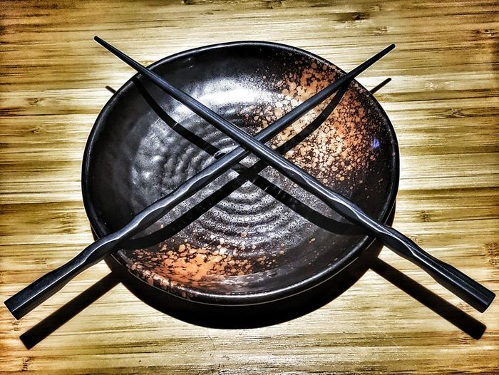 High Angle View Of Chopsticks On Plate Over Table