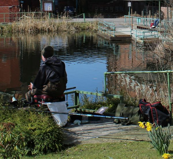 Casual Clothing Fisherman Fishing Flowers. Daffodils. Full Length Grass Leisure Activity Lifestyles Male Men Outdoors Outdoors. Portrait Rear View River Single Sitting Sport. Tranquility. Tree Water Water Reflections