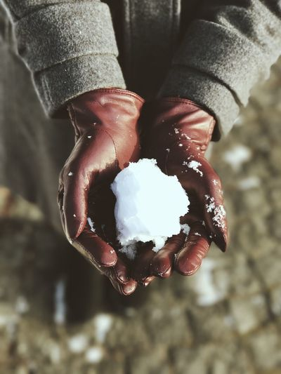 High Angle View Of Person's Hands Holding Snow