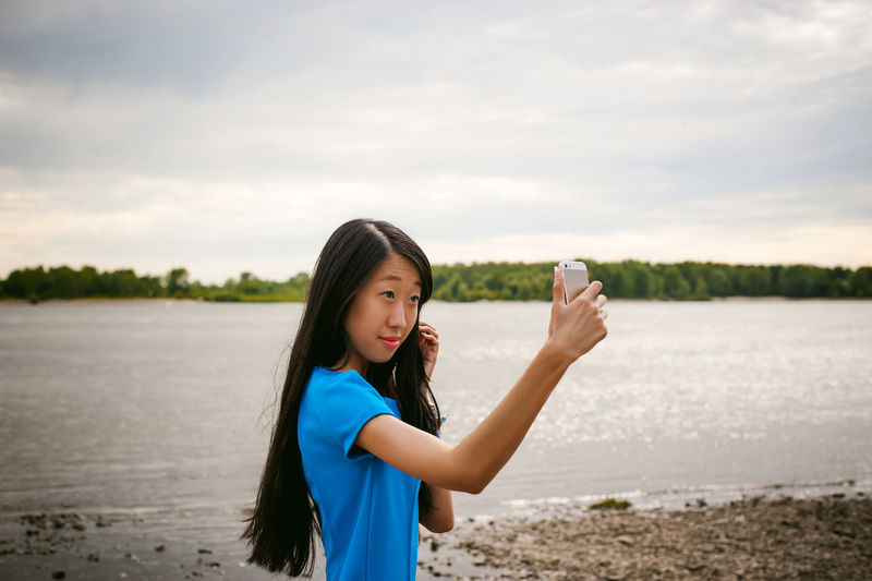 Young woman taking selfie while standing at riverbank
