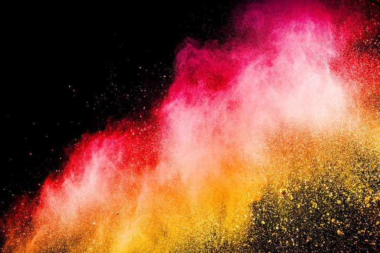 Defocused image of multi colored powder paints against black background