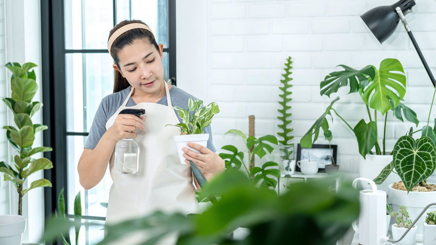 Young woman looking away while standing on potted plant