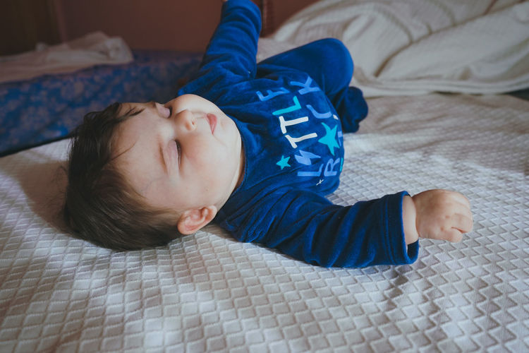 Cute baby sleeping on bed at home