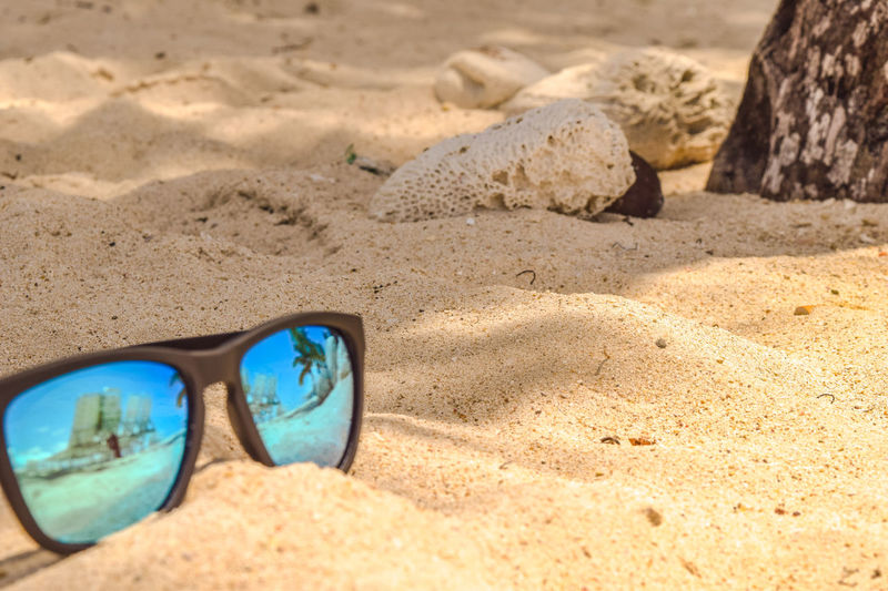 Sunglassen in a beach lying in the white sand, Dominican Republic Holiday Modern Palm Poster Reflection Shining Sunny Accessoires Bacardi Island Beach Blue Glasses Coast Glass Idyllic Island Ocean Palm Reflection Protection Shadow Style Summer Sun Tropical Climate Wallpaper White Beach