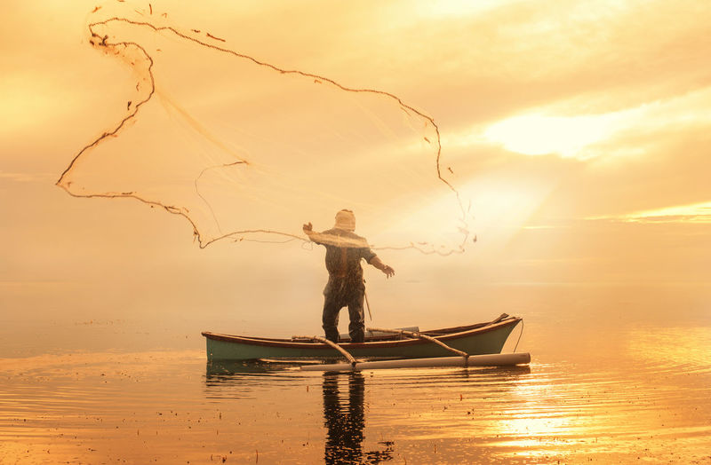 Fisherman With Fishing Net On Boat In Sea During Sunset