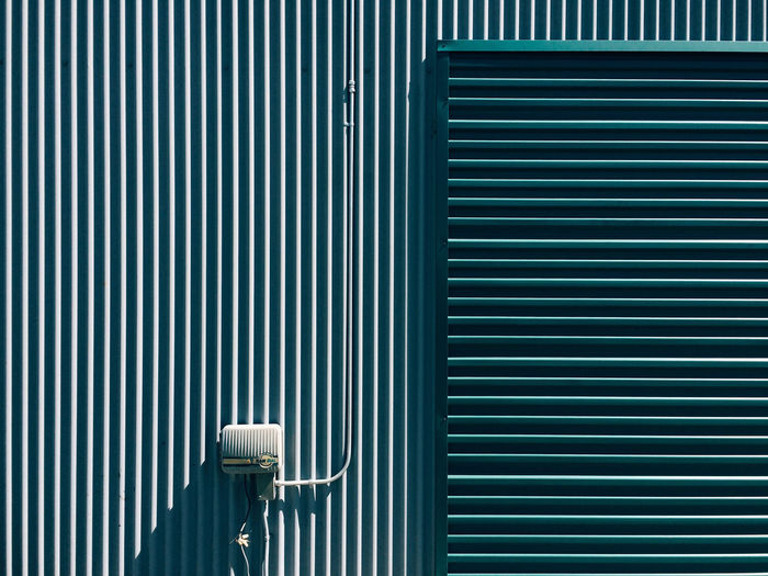 Security camera on striped wall during sunny day