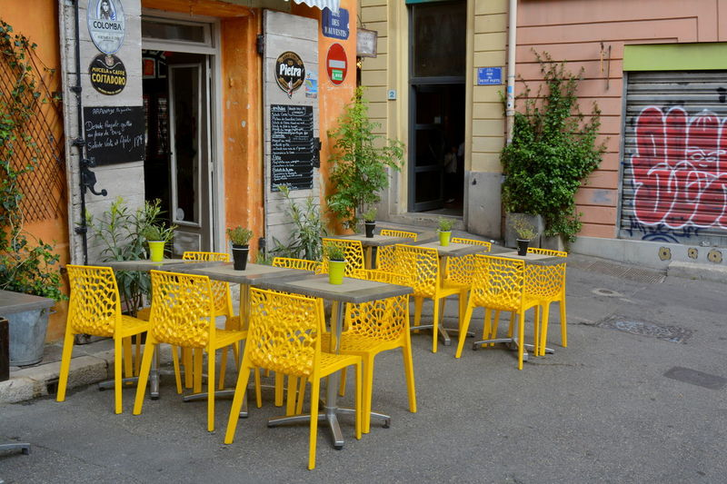 Empty chairs and tables at sidewalk cafe in city