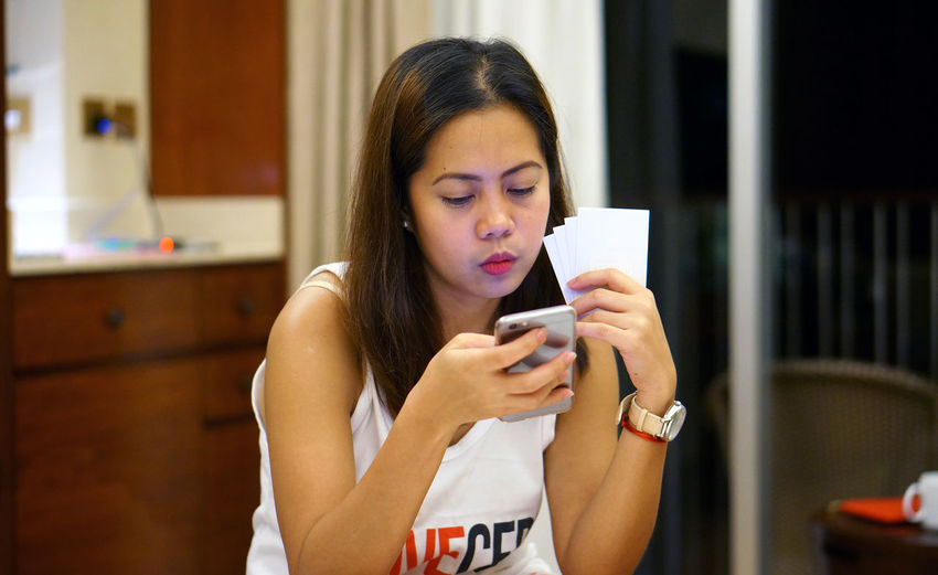 Woman using smart phone while playing card at home