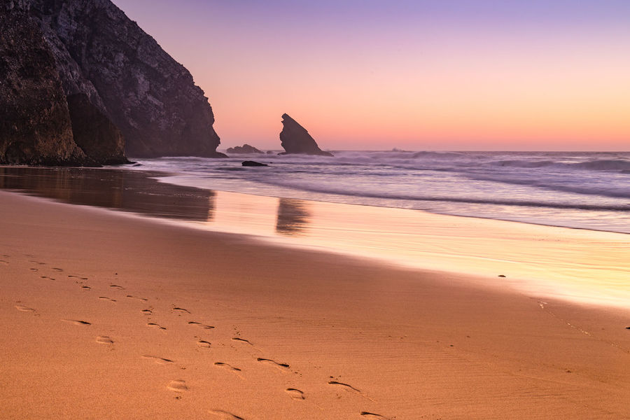 A sunset view of Praia da Adraga in the coast of Portugal Adraga Adraga Beach Beach Beach Photography Beauty In Nature Coastline Horizon Over Water Lisbon Non-urban Scene Orange Color Outdoors Playa Portugal Praia Da Adraga Remote Scenics Sea Shore Sintra Sunset Tourism Tranquil Scene Travel Destinations Water Wave