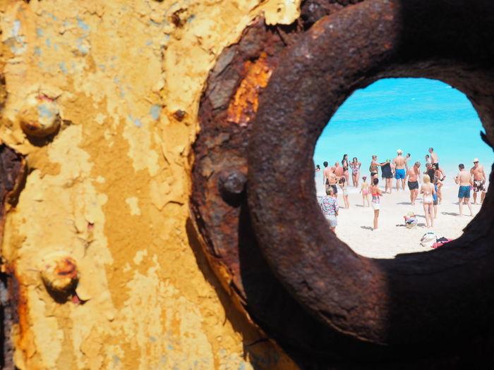 People seen through hole in rusty metal