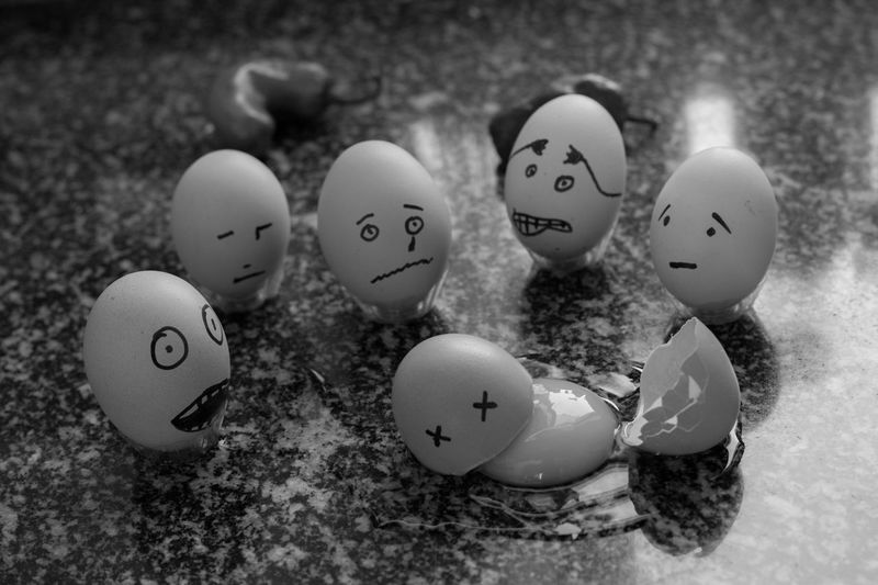 Various anthropomorphic faces on eggshells at table