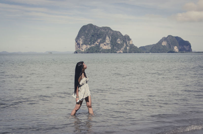 Young Woman Looking Up While Standing In Sea Against Sky