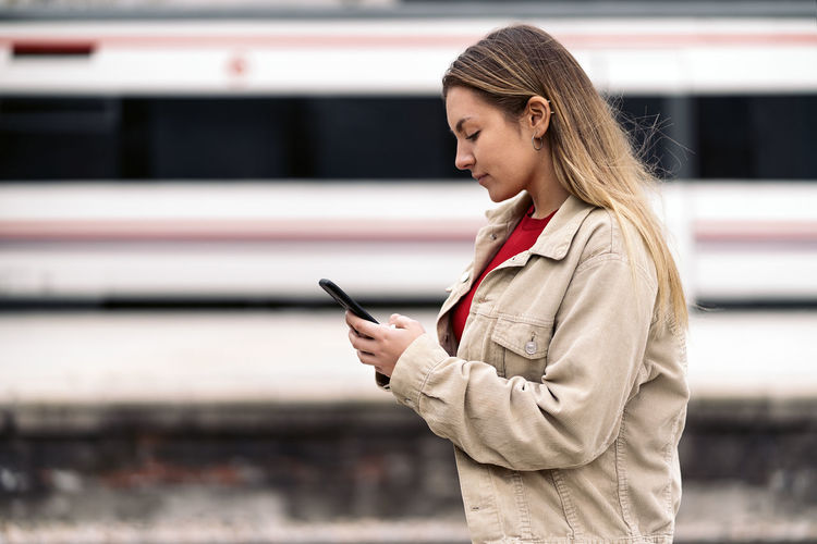 Young woman looking away while standing on mobile phone