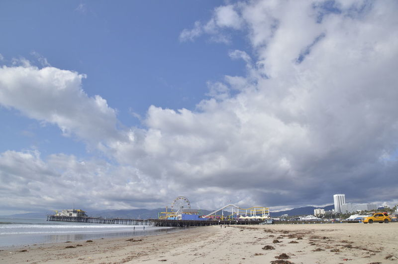 Distant View Of Santa Monica Pier At Beach Against Sky