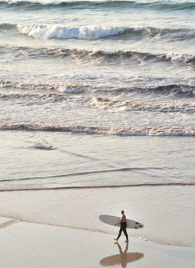 Man with surfboard on beach