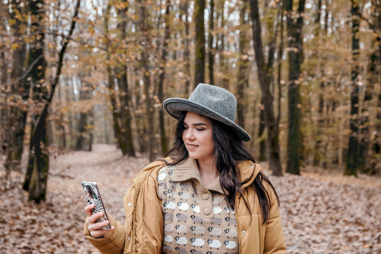 Young woman using mobile phone, texting. walking in woods, forest, autumn, fall.