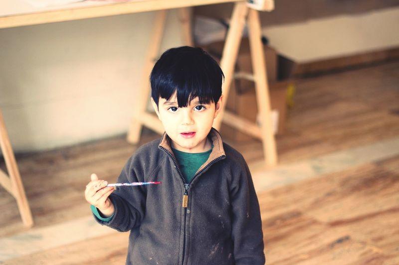 Portrait of boy holding paintbrush on hardwood floor