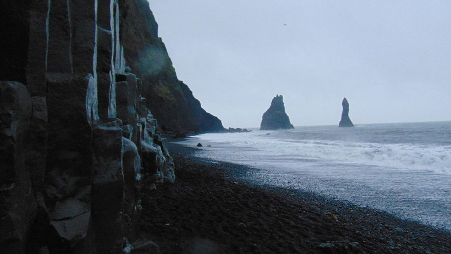 The Vikings had a legend that the rocks at this beach were tyrolls turned to stone as the sun rised while they attempted to drag ships to the shore. Basalt Columns Black Beach Sand Iceland North Atlantic Ocean Rainstorm Reynisfjara Trolls