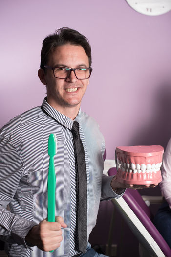 Portrait of dentist holding denture and toothbrush
