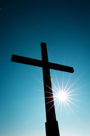 Low angle view of cross against blue sky