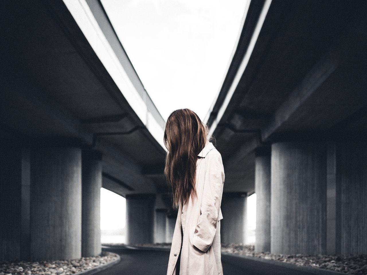 Side View Of Woman Standing In Corridor
