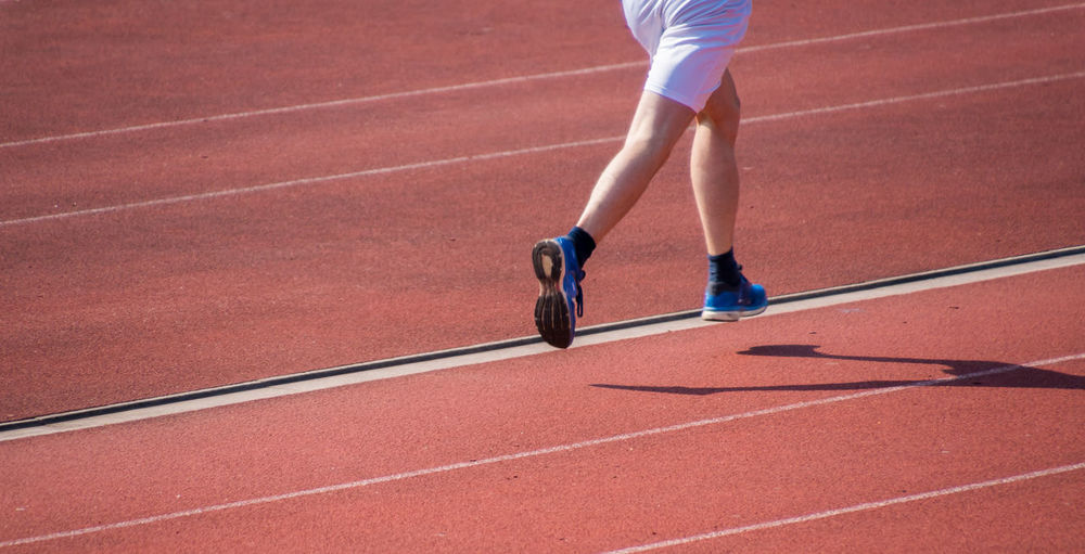 Low section of male athlete running on sports track