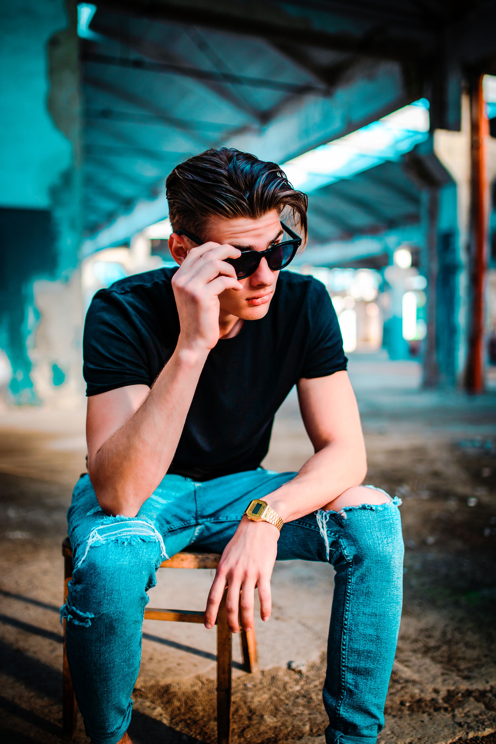 sitting, one person, young adult, fashion, real people, glasses, casual clothing, young men, lifestyles, sunglasses, leisure activity, focus on foreground, architecture, front view, full length, three quarter length, built structure, outdoors, architectural column
