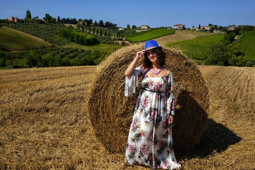 beautiful woman between round bales Woman Agriculture Beauty In Nature Crop  Day Environment Farm Fashion Field Front View Land Landscape Leisure Activity Nature One Person Outdoors Plant Real People Round Bale Rural Scene Sky Smiling Standing Sunlight