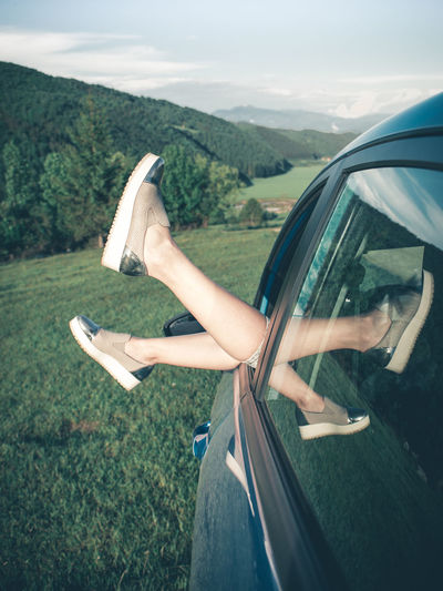 Summer road trip car vacation concept. Woman legs out the windows in car. Conceptual freedom, travel and holidays image. Happy Lifestyle Summertime Vacations Close-up Concept Day Grass Human Body Part Human Hand Legs Leisure Activity Nature One Person Outdoors People Real People Road Road Trip Sky Summer Transportation Tree Vacation Young Adult A New Perspective On Life