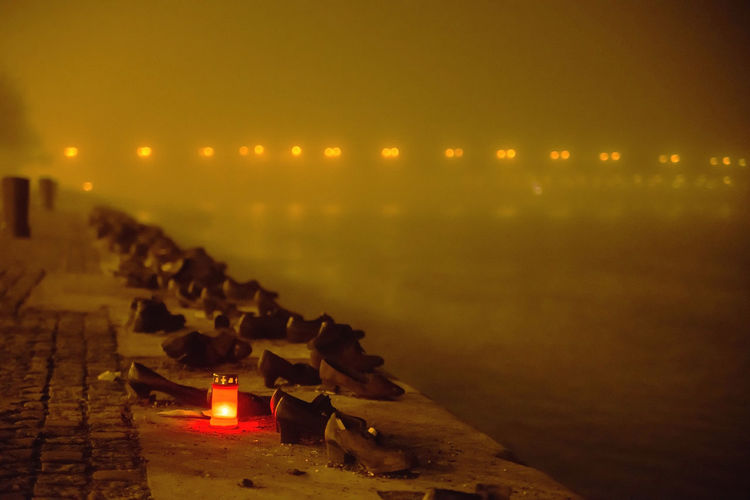 Shoes on the Danube Bank candles at the memorial, Budapest Hungary Flame Illuminated Burning Fire Heat - Temperature Candle Lighting Equipment Sky Fire - Natural Phenomenon In A Row Architecture Nature No People Religion Sunset Built Structure Celebration Building Holiday Glowing Electric Lamp