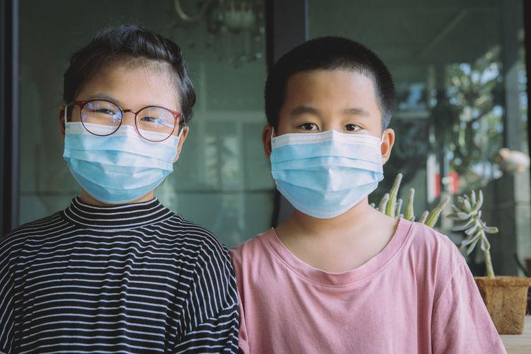 Portrait of siblings wearing masks